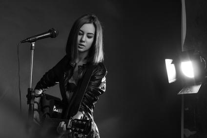 Chanteuse en solo de guitare dans un studio